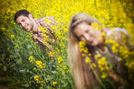 Young couple in colza field playing hide and seek, Tuscany, Italy