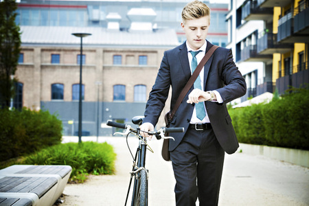 Young businessman checking the time, Munich, Bavaria, Germany
