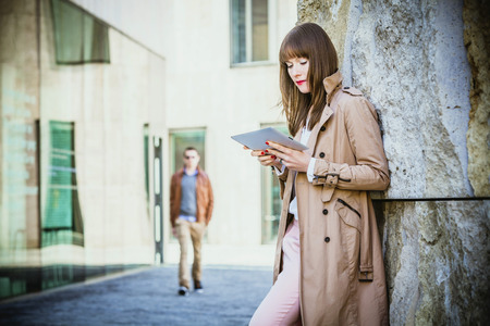 Young woman using digital tablet outdoors, Munich, Bavaria, Germany LANG_EVOIMAGES