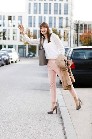 Young woman hailing a taxi outdoors, Munich, Bavaria, Germany