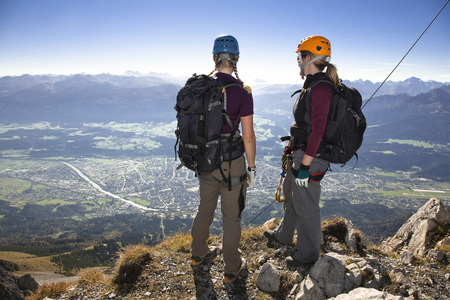 Female Alpinists standing on mountain top, looking at view, Innsbruck route, Tyrol, Austria LANG_EVOIMAGES