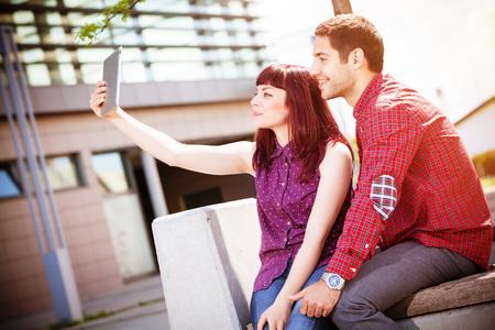 Young couple using digital tablet outdoors, Osijek, Croatia LANG_EVOIMAGES