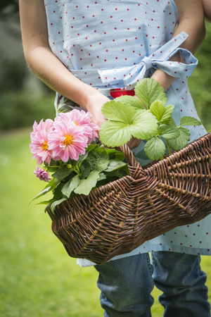 Girl gardening, carrying basket with flowers