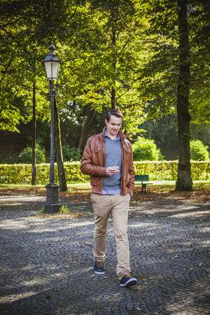 Young man text messaging outdoors, Munich, Bavaria, Germany
