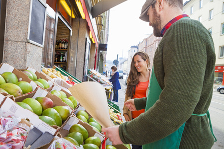 grocer: Grocer and customer looking at fruit variety