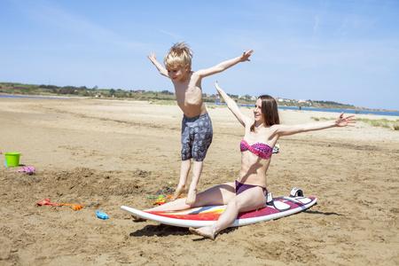 niño sin camisa: Madre e hijo jugando con tabla de surf en la playa LANG_EVOIMAGES