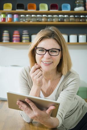 silver surfer: Senior woman in kitchen using tablet pc, portrait