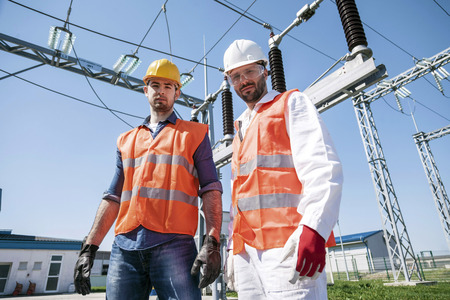 Portrait of two engineers against electricity substation