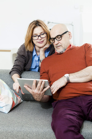 silver surfer: Senior couple using digital tablet at home LANG_EVOIMAGES