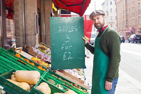 grocer: Greengrocers Shop, grocer holding price tag