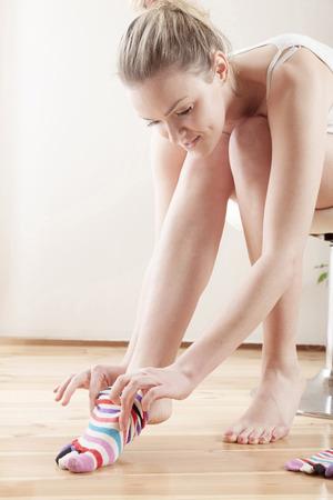 Young woman putting on socks