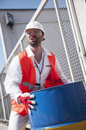Engineer checking metal drum in electricity substation LANG_EVOIMAGES