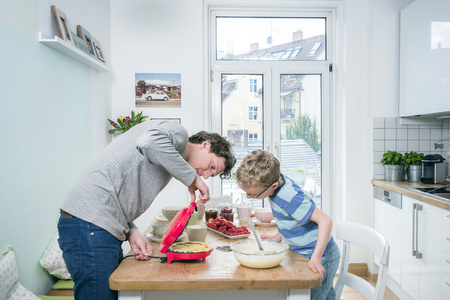 Father and son baking waffles in kitchen LANG_EVOIMAGES