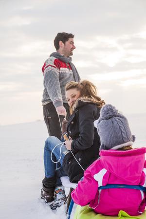 Happy family sledging in snow
