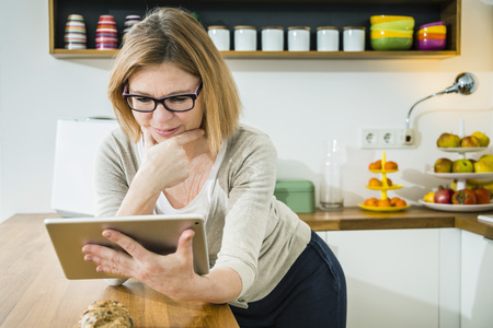 silver surfer: Senior woman in kitchen using tablet pc