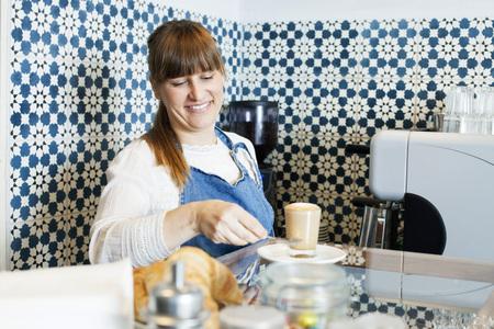 Female barista preparing latte