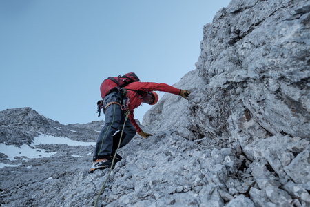 conquering adversity: Mountaineer climbing steep wall in mountain range LANG_EVOIMAGES