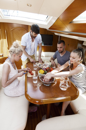 Group of friends eating in cabin of yacht, Adriatic Sea