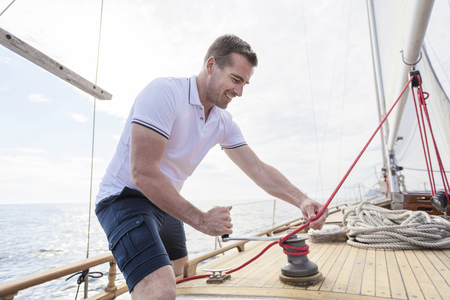 turn away: Man winding rope with cable winch on sailboat