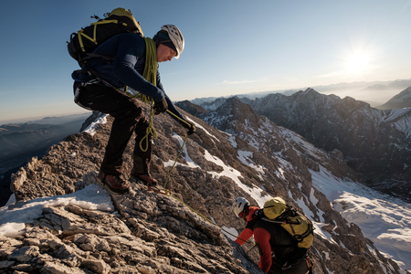 conquering adversity: Two mountaineers climbing mountain peak in European Alps