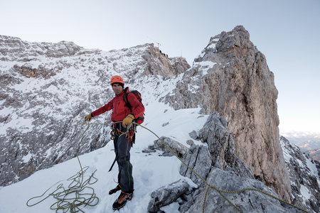 Mountain guide adjusting rope on cliff in mountain range LANG_EVOIMAGES