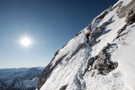 conquering adversity: Two mountaineers climbing a snowcapped wall in European Alps