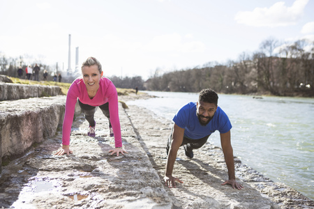 Young couple doing push-ups by the riverside