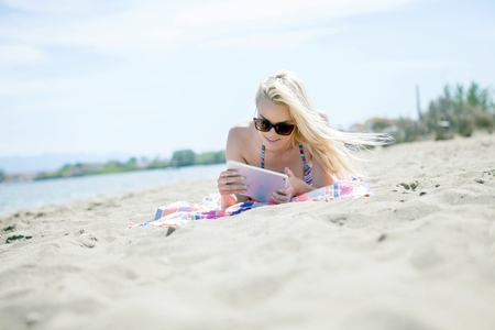 Young woman using digital tablet on beach