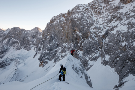 conquering adversity: Two mountaineers moving up snowcapped cliff in mountain range
