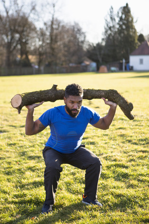 conquering adversity: Young man doing squats with tree trunk on shoulder