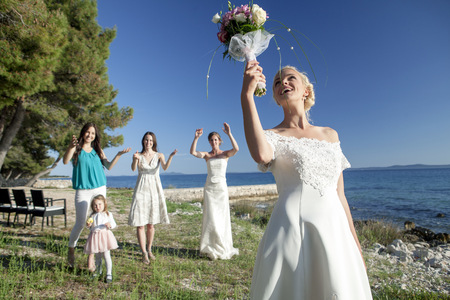 girls at the beach series: Bride throwing bouquet at wedding reception