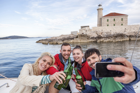 Group of friends drinking beer on sailboat, Adriatic Sea