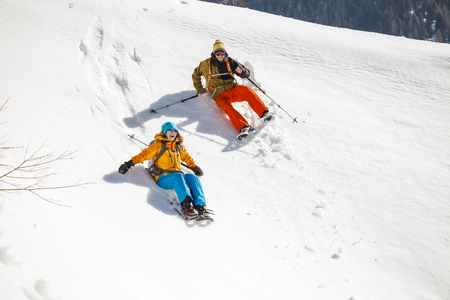 snowshoes: Two people with snowshoes falling on powder snow LANG_EVOIMAGES