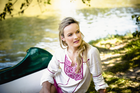 people: Young woman sits on the riverside, foothills of the Alps, Bavaria, Germany