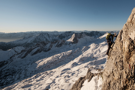 conquering adversity: Lone mountaineer climbing steep wall in European Alps