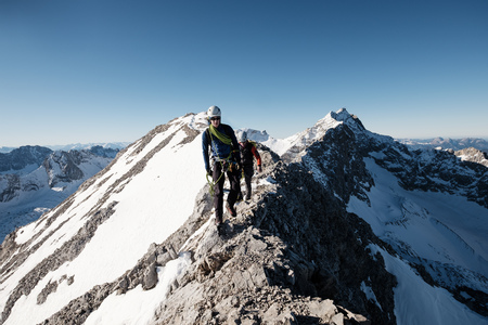 Two mountaineers hiking on mountain peak in European Alps LANG_EVOIMAGES