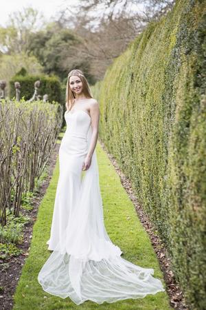 Bride showing off wedding dress outdoors LANG_EVOIMAGES