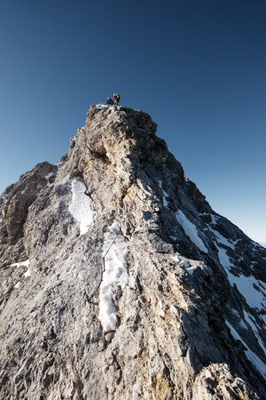 conquering adversity: Two mountaineers standing on mountain peak in European Alps