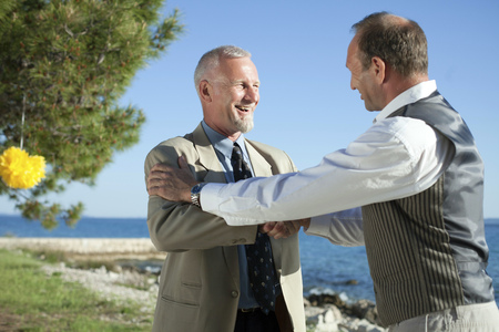 Father of the bride shaking hands with wedding guest LANG_EVOIMAGES