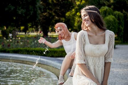 Young women in hippie style fashion splashing water