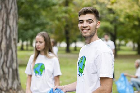 altruismo: Teenage volunteers doing garbage cleanup in park LANG_EVOIMAGES