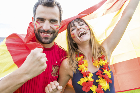 bandera croacia: Young couple with face paint waving Spanish flag