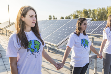 environmental issues: Group of teenage environmentalists holding hands LANG_EVOIMAGES