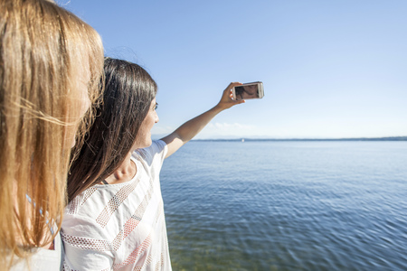 Two young women taking selfie by lake