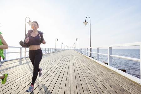 vanishing point: Two women jogging along a jetty