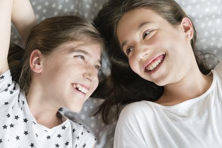 Two teenage girls relaxing in bedroom