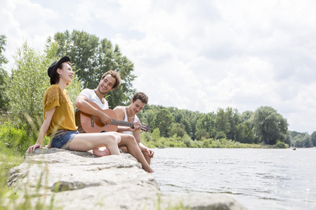 plucking: Group of friends relaxing on riverbank