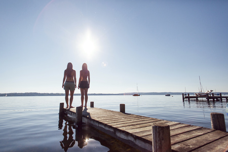 Two young women standing on pier by lake