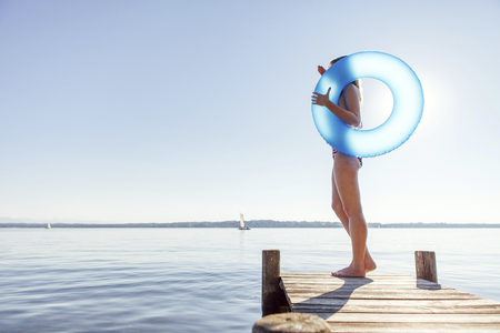 Young woman stands on pier by lake holding inflatable ring