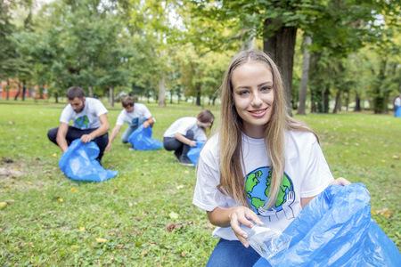 environmental issues: Teenage volunteers doing garbage cleanup in park LANG_EVOIMAGES